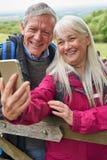 Coppie senior sorridenti che fanno un'escursione nel portone e nella presa facenti una pausa della campagna del Selfie sul telefo fotografie stock libere da diritti