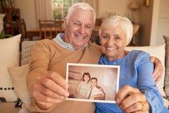 Coppie senior sorridenti che tengono una foto dei loro auto giovanili Immagine Stock