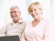 Coppie senior sorridenti con il computer portatile Immagini Stock