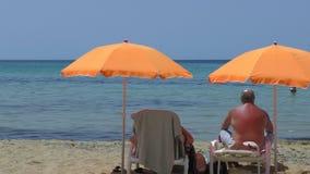 Coppie senior sotto gli ombrelli sulla spiaggia archivi video