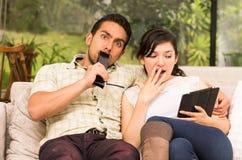 Coppie sorprese sveglie che stringono a sé nel sofà mentre Fotografia Stock