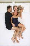 Coppie sorridenti abbracciate sul letto Fotografia Stock Libera da Diritti