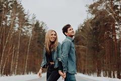 Coppie sorridenti allegre felici dei giovani nei vestiti del denim in foresta nevosa nell'inverno sulla strada Posto per testo immagine stock
