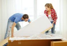 Coppie sorridenti che aprono grande scatola di cartone con il sofà Fotografie Stock