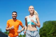 Coppie sorridenti che corrono all'aperto Immagine Stock Libera da Diritti