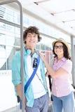 Coppie sorridenti che distolgono lo sguardo mentre aspettando alla fermata dell'autobus Fotografie Stock Libere da Diritti