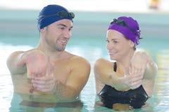 Coppie sorridenti che fanno aerobica dell'acqua nella piscina immagine stock