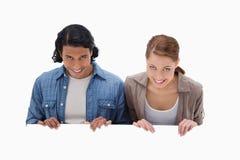 Coppie sorridenti che guardano sopra la parete in bianco Immagini Stock