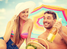 Coppie sorridenti che hanno picnic sulla spiaggia Fotografie Stock Libere da Diritti