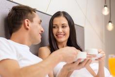 Coppie sorridenti che mangiano prima colazione a letto in hotel fotografia stock