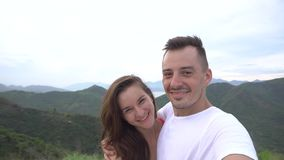 Coppie sorridenti che prendono selfie in montagne, vista aerea della città La donna bacia l'uomo archivi video