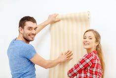 Coppie sorridenti che scelgono carta da parati per la nuova casa Fotografie Stock Libere da Diritti
