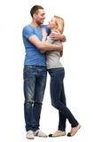 Coppie sorridenti che se abbracciano e che esaminano Immagini Stock