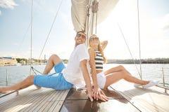 Coppie sorridenti che si siedono sulla piattaforma dell'yacht Fotografie Stock