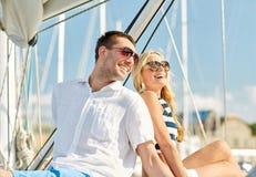 Coppie sorridenti che si siedono sulla piattaforma dell'yacht Fotografia Stock
