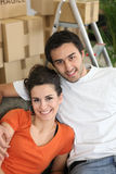 Coppie sorridenti che si siedono in un sofà Fotografia Stock
