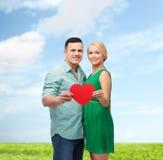 Coppie sorridenti che tengono grande cuore rosso Fotografia Stock Libera da Diritti
