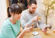 Coppie sorridenti con gli smartphones che bevono tè Fotografie Stock Libere da Diritti