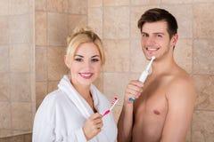 Coppie sorridenti con i denti di spazzolatura in bagno fotografia stock libera da diritti