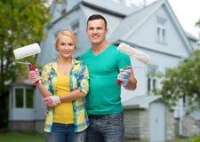 Coppie sorridenti con i rulli di pittura sopra la casa Fotografia Stock Libera da Diritti