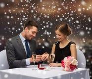 Coppie sorridenti con il contenitore di regalo rosso al ristorante Immagini Stock Libere da Diritti