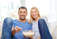 Coppie sorridenti con il film di sorveglianza del popcorn a casa immagini stock
