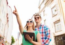 Coppie sorridenti con il pc della compressa in città Immagine Stock Libera da Diritti