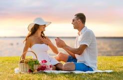 Coppie sorridenti con il piccolo contenitore di regalo rosso sul picnic Immagini Stock