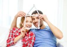 Coppie sorridenti con la casa dal nastro di misurazione Fotografia Stock Libera da Diritti