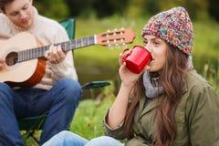 Coppie sorridenti con la chitarra nel campeggio fotografia stock