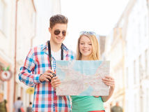 Coppie sorridenti con la macchina fotografica della foto e della mappa in città Fotografie Stock
