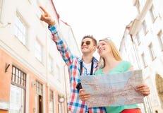 Coppie sorridenti con la macchina fotografica della foto e della mappa in città Immagine Stock