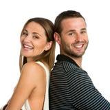 Coppie sorridenti con le parti posteriori insieme. Immagine Stock Libera da Diritti