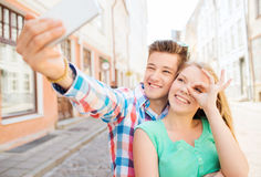 Coppie sorridenti con lo smartphone in città Immagini Stock Libere da Diritti