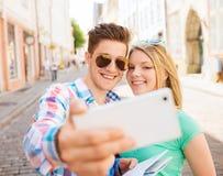 Coppie sorridenti con lo smartphone in città Immagini Stock