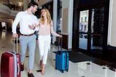 coppie sorridenti dei viaggiatori che camminano con i bagagli fotografie stock libere da diritti