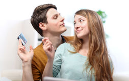 Coppie sorridenti divertenti facendo uso della carta di credito al negozio di Internet online Fotografia Stock