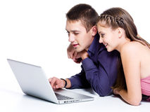 Coppie sorridenti felici che esaminano computer portatile Immagini Stock Libere da Diritti