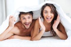 Coppie sorridenti felici che si trovano a letto coperto di coperta Fotografia Stock