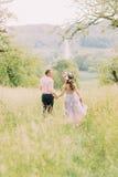Coppie sorridenti felici che tornano indietro nel tenersi per mano del giardino della fioritura Fotografie Stock Libere da Diritti