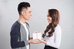 Coppie sorridenti felici nell'amore che controlla fondo grigio Fotografia Stock
