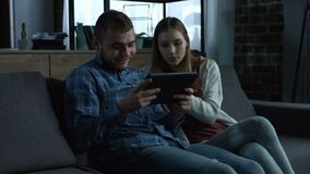 Coppie sorridenti giovani con la compressa che si rilassa sul sofà archivi video