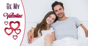 Coppie sorridenti a letto con le forme del cuore ed il testo rossi del biglietto di S. Valentino Fotografia Stock