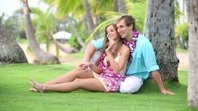 Coppie sorridenti nell'amore con Lei, sedendosi ed abbracciando sotto la palma video d archivio