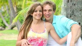 Coppie sorridenti nell'amore, sedendosi ed abbracciando sotto la palma stock footage