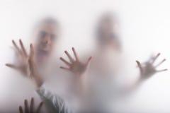 Coppie spaventate dietro la finestra Fotografia Stock Libera da Diritti