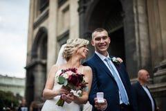 Coppie, sposa felice e sposo posanti con la fede nuziale, chiesa Fotografia Stock Libera da Diritti