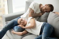 Coppie stanche rilassate che dormono avendo pelo sul tog comodo del sofà fotografia stock libera da diritti