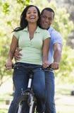 Coppie su una bici all'aperto che sorride Fotografia Stock