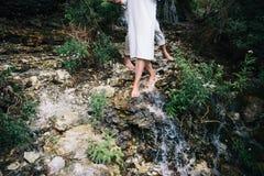 Coppie sui precedenti della torrente montano piede che cammina attraverso la cascata, springwater Immagine Stock